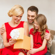 Stock Photo: Happy family opening gift box