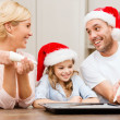 Happy family in santa helper hats making cookies — Stock Photo #35282621
