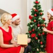 Smiling family decorating christmas tree — Stock Photo #35282937
