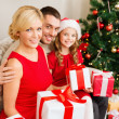 Smiling family holding many gift boxes — ストック写真