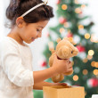 Stock Photo: Happy child girl with gift box and teddy bear
