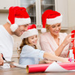 Smiling family in santa helper hats with gift box — Zdjęcie stockowe