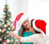 Hugging mother and daughter in santa helper hats — Stock Photo