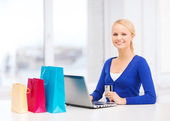 Woman with shopping bags, laptop and credit card — Stock Photo