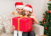 Smiling father and daughter opening gift box — Stock Photo