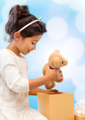 Happy child girl with gift box and teddy bear — Stock Photo