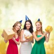 Three smiling women in blue hats with gift boxes — Stock Photo #35341673