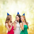 Three smiling women in hats blowing favor horns — Stock Photo #35343603