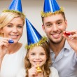 Smiling family in blue hats blowing favor horns — Stock Photo #35348061