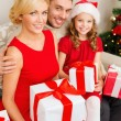 Smiling family holding many gift boxes — Стоковая фотография
