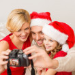 Smiling family in santa helper hats taking picture — Stock Photo #35348803