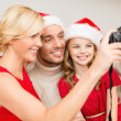 Stock Photo: Smiling family in santhelper hats taking picture
