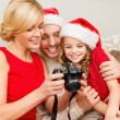 Family in santa helper hats looking at pictires — Stock Photo #35349299