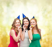 Three smiling women in hats blowing favor horns — 图库照片