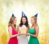 Three smiling women in blue hats with gift box — Foto Stock