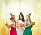 Three smiling women in blue hats with gift boxes — 图库照片