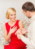 Romantic man proposing to a woman in red dress — Stok fotoğraf