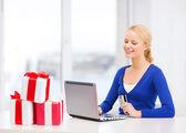 Hediyeler, dizüstü bilgisayar ve kredi kartı ile kadın — Stok fotoğraf