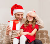 Smiling father surprises daughter with gift box — Stock Photo