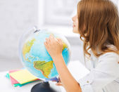Curious student girl with globe at school — Stock Photo