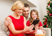 Smiling family with tablet pc — Stockfoto