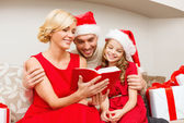 Smiling family reading book — Stock Photo