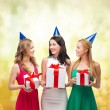 Three smiling women in blue hats with gift boxes — Stock Photo #35356471