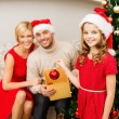 Smiling family decorating christmas tree — Stock fotografie