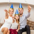Smiling family in blue hats with cake — Stock Photo #35369585