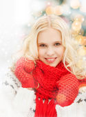 Smiling teenage girl in red mittens and scarf — Stock Photo