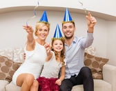 Smiling family in blue hats with cake — Stock Photo