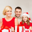 Smiling family holding many gift boxes — Стоковое фото