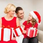 Smiling family holding many gift boxes — Stock Photo #35370029