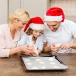 Happy family in santa helper hats making cookies — Stock Photo #35370091