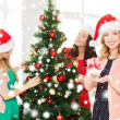 Women in santa helper hats decorating a tree — Foto Stock