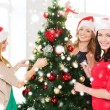 Women in santa helper hats decorating a tree — Stock Photo #35429859
