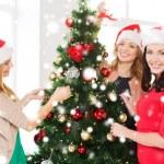 Women in santa helper hats decorating a tree — Stock Photo