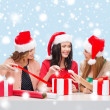 Smiling women in santa helper hats with gift boxes — Lizenzfreies Foto