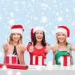 Smiling women in santa helper hats with gift boxes — Stock fotografie