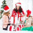 Women in santa helper hats with many gift boxes — Stock fotografie