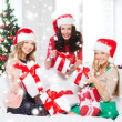 Women in santa helper hats with many gift boxes — Stock Photo #35429963