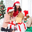 Women in santa helper hats with many gift boxes — Stock Photo #35429981