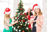 Women in santa helper hats decorating a tree — Stok fotoğraf