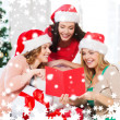 Women in santa helper hats with card and gifts — Stockfoto