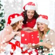 Women in santa helper hats with card and gifts — Stok fotoğraf