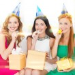 Three women wearing hats with gifts blowing horns — Stock Photo #35430041
