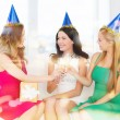 Three women wearing hats with champagne glasses — Stock Photo #35430077