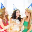 Three women wearing hats with champagne glasses — Stock Photo #35430145