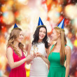 Three women wearing hats with champagne glasses — Stock Photo #35430167