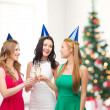 Three women wearing hats with champagne glasses — Stock Photo #35430191